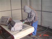 喷砂房里面正在操作的工人示例